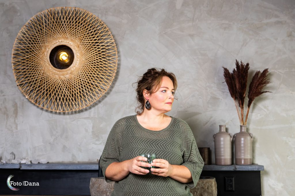 Vrouw met groene trui, kijkt opzij met glas water in handen