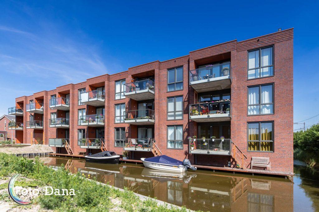 Appartementencomplex met bootjes ervoor, blauwe lucht