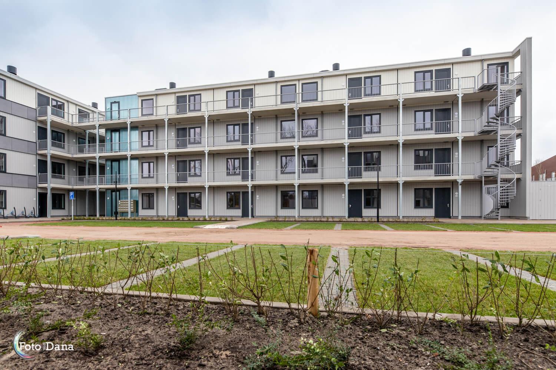 Modulaire woningcomplex Regioplein Schagen met groene parkeervlakken en tuintje ervoor.