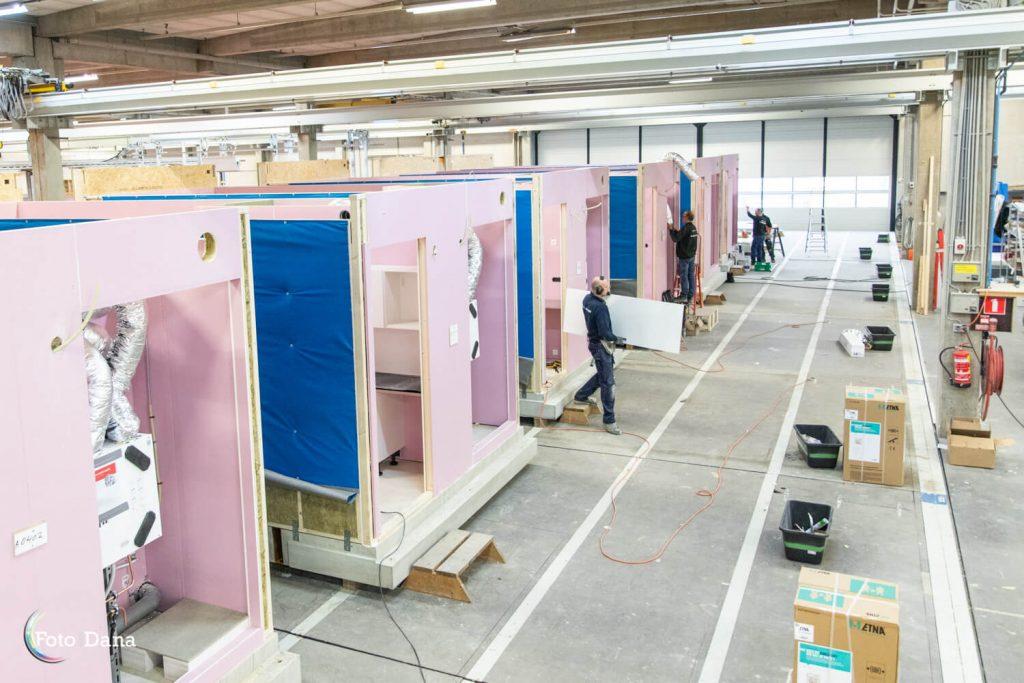 van bovenaf zes modules in fabriekshal die ingetimmerd worden