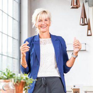 lachende vrouw bij groot raam, blond haar en blauw jasje. Ze lacht en is relaxt.