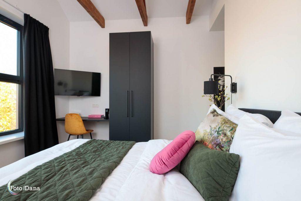 hotelkamer met balkenplafond bed en bureau