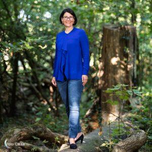 Buitenportret vrouw met halflang zwart haar, een bril op en fel blauw shirt staat op een boomstam