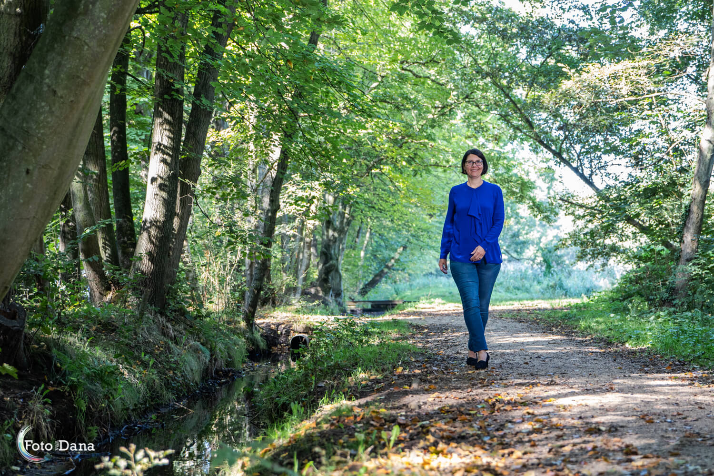 Loopfoto vrouw met blauw shirt in park met watertje links