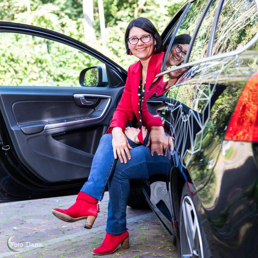 Buitenportret vrouw met halflang zwarthaar en bril op zit half in auto. rode laarsjes en rode jas