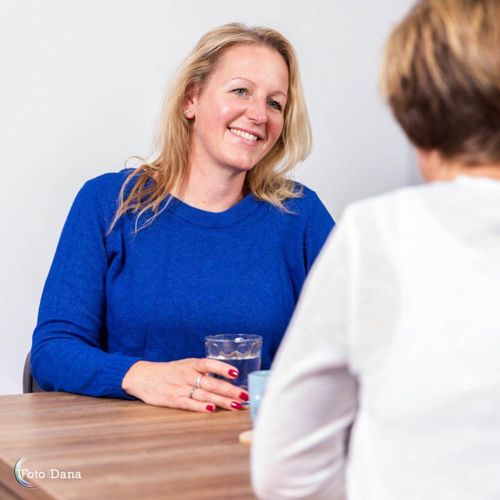 Overleg coach Esther met client. Coach lacht bemoedigend en heeft rode nagellak en een glas water