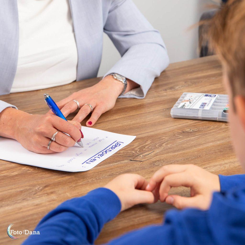 Close-up van overleg coach met kind met lijstje leerdoelen
