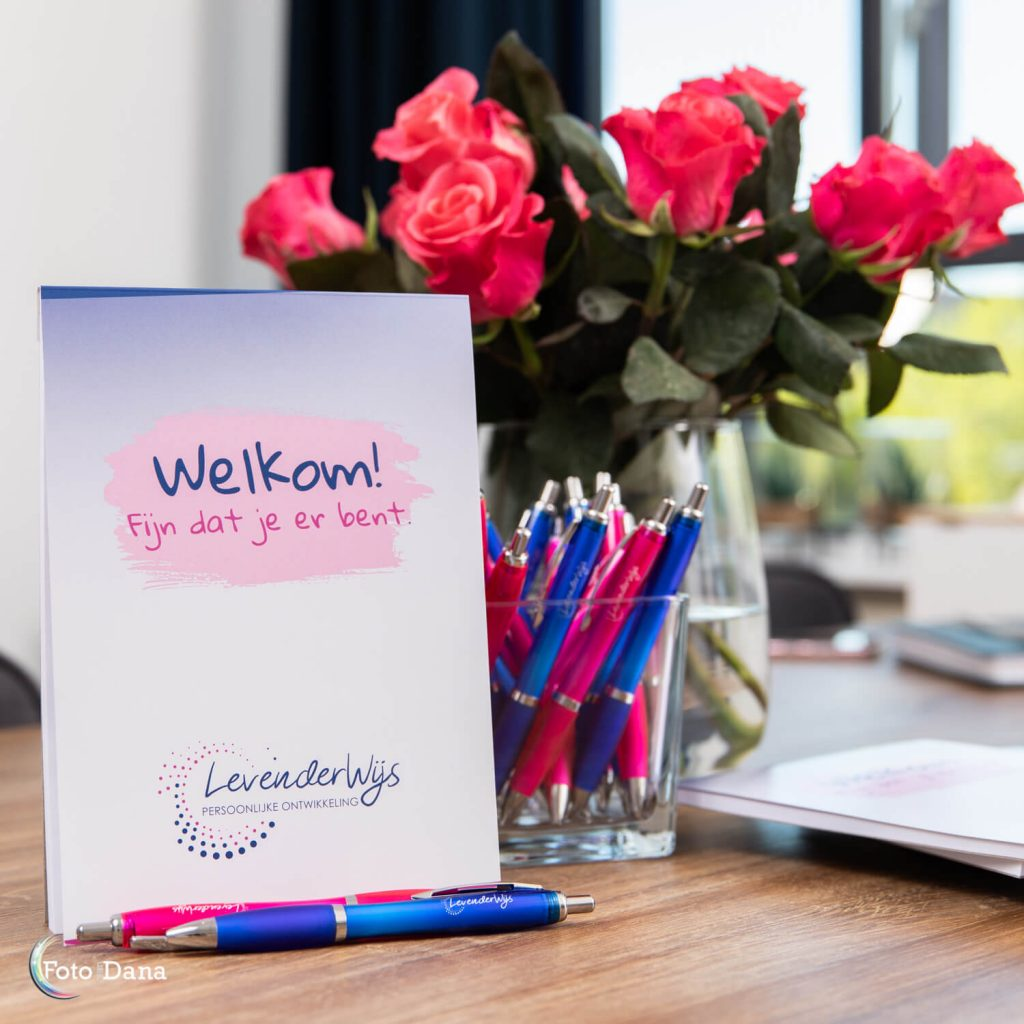 personal branding notitieblok en pennen van Levenderwijs met vaas met rode rozen op achtergrond