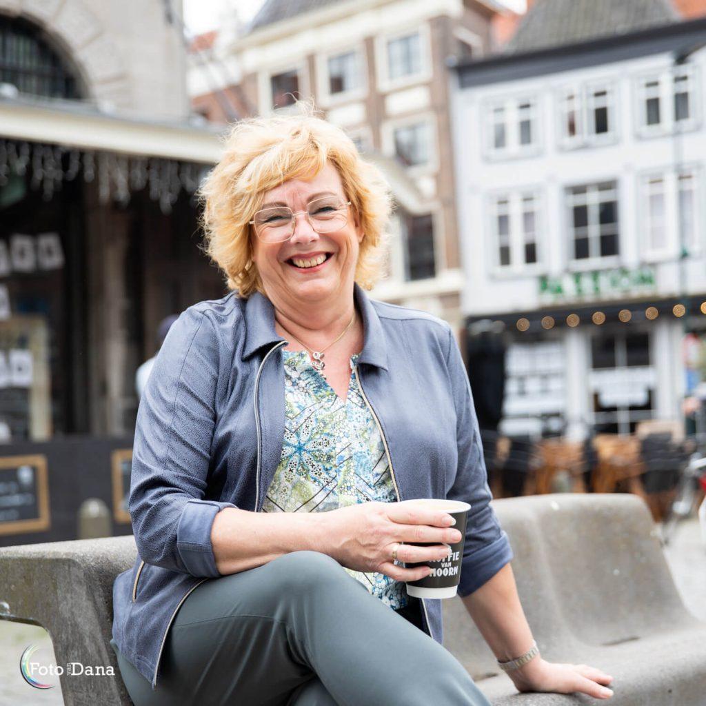 Lachende vrouw op bankje buiten met paars jasje, bril op en koffie in haar hand