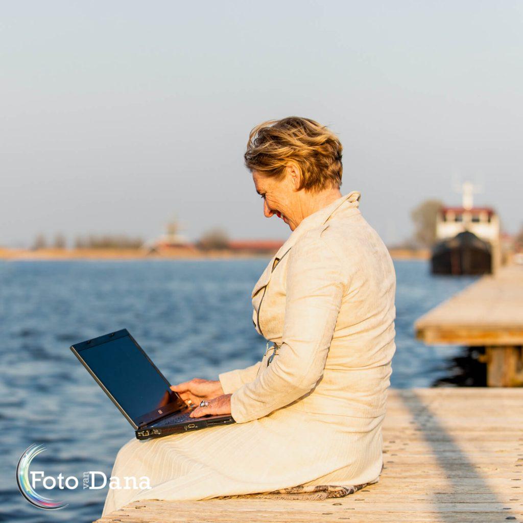 Marianne zit op steiger op haar laptop werkend in de avondzon. Bootje op de achtergrond.