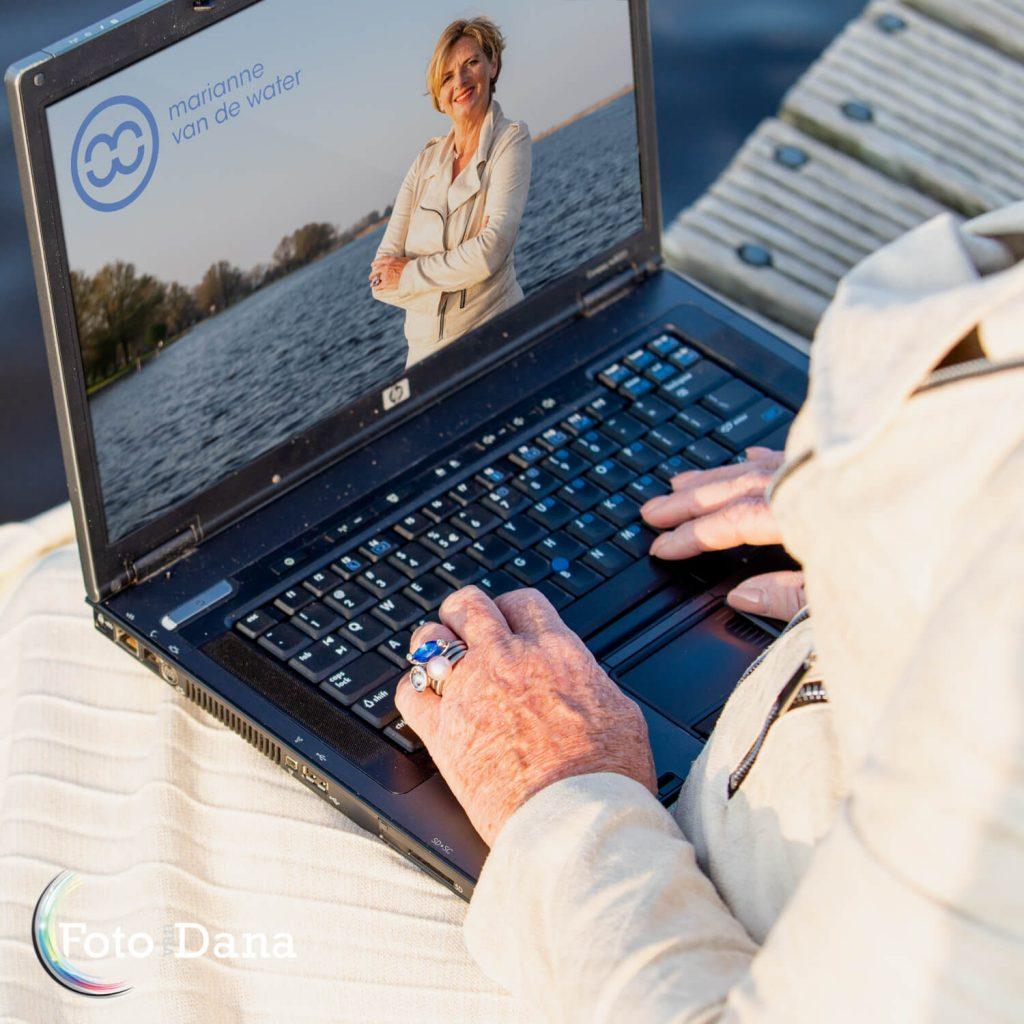 Over schouder meekijkend naar laptop met website van Marianne van de Water