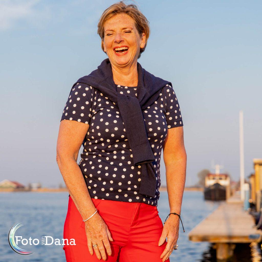 Lachende vrouw met ogen dicht in de avondzon in de haven met een steiger en bootje op achtergrond