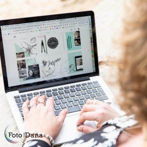 Vanaf schouder Janneke meekijkend op haar laptop met haar website op het scherm