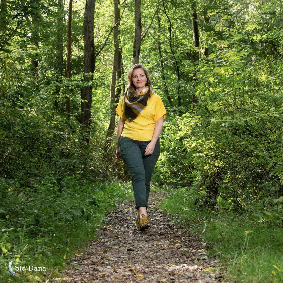 Femke loopt op mij af in geel shirt in een groen park