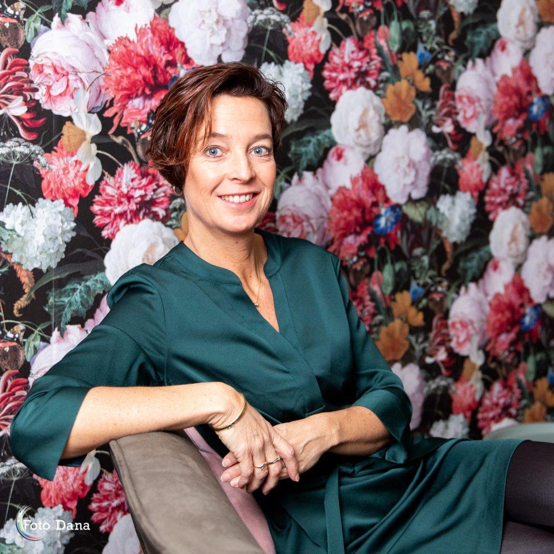 ondernemende vrouw met groene jurk bij bloemetjesbehang