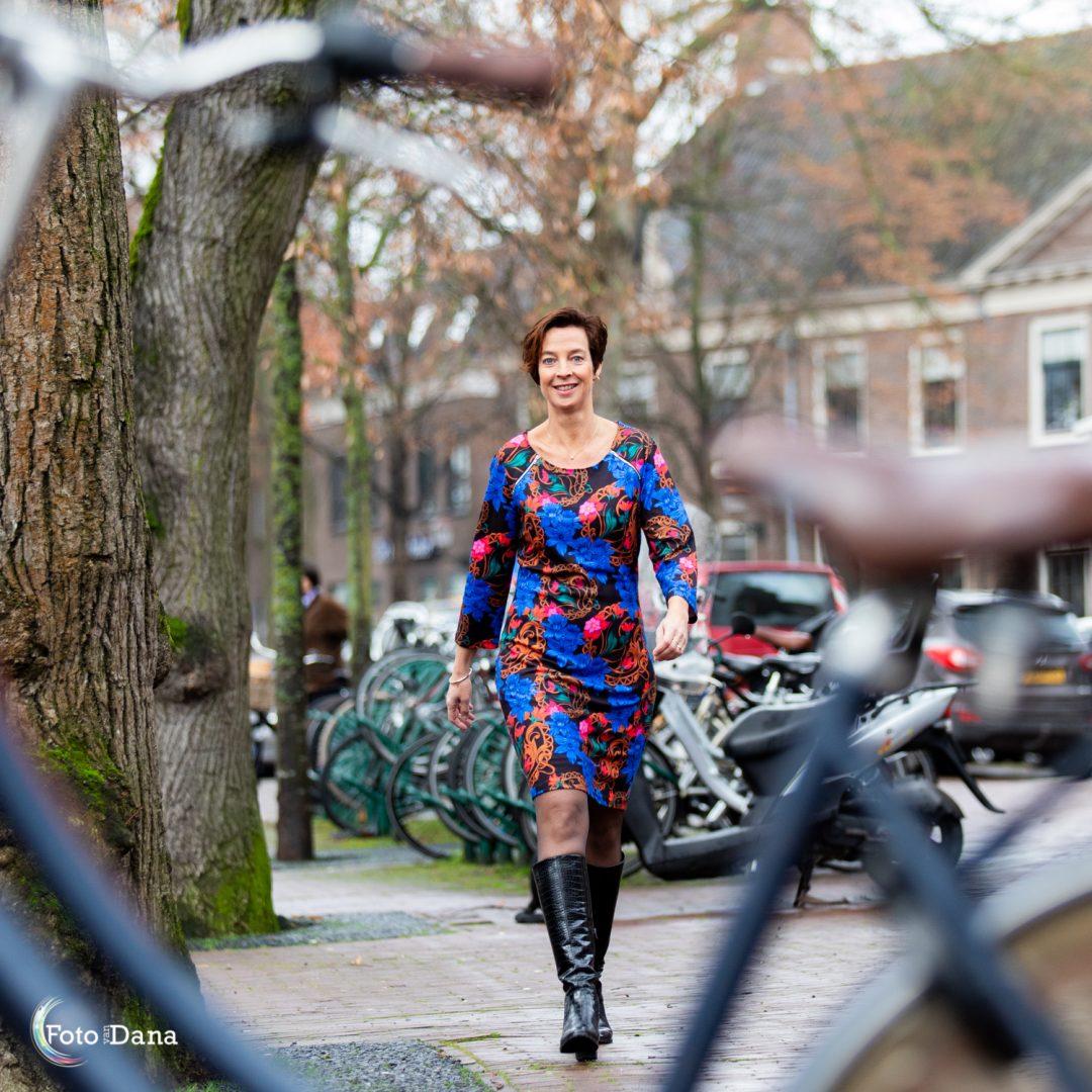 ondernemende vrouw in kleurige jurk loopt naar fiets toe