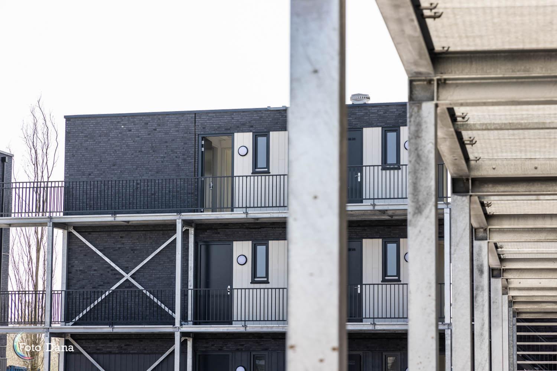 doorkijk vanaf galerij naar grijze driekamer modulaire woning