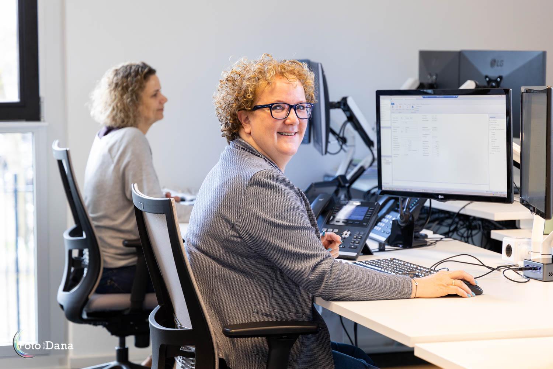 twee vrouwen aan het werk achter computer 1 vrouw kijkt in camera