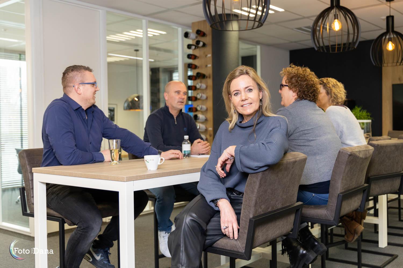 overleg vier personen aan hoge tafel vrouw is naar camera gedraaid